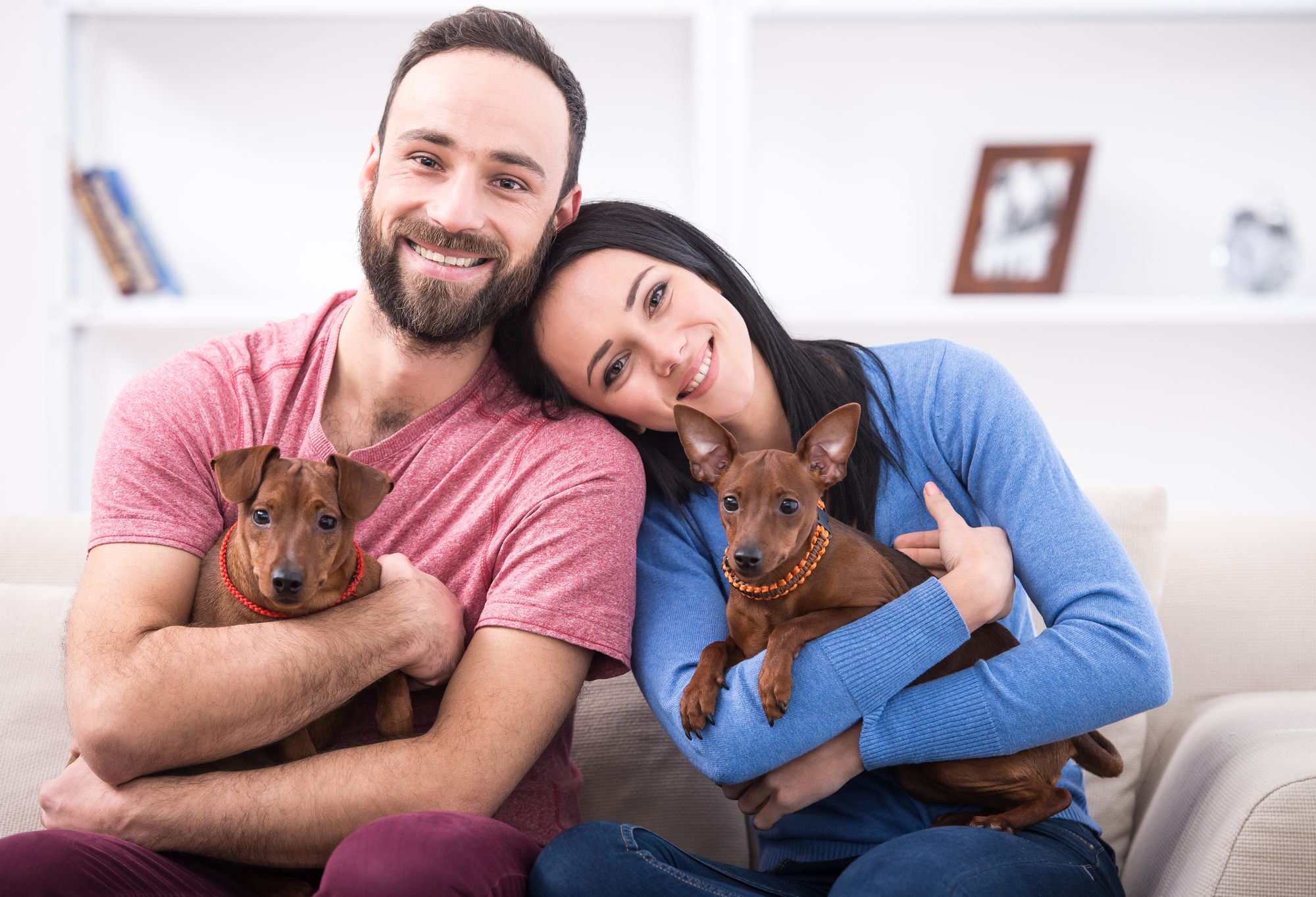 A man and a woman holding brown dogs